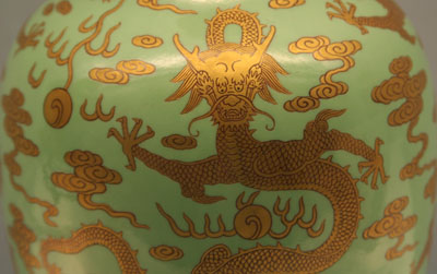 Vase with a golden dragon and cloud design on a green background